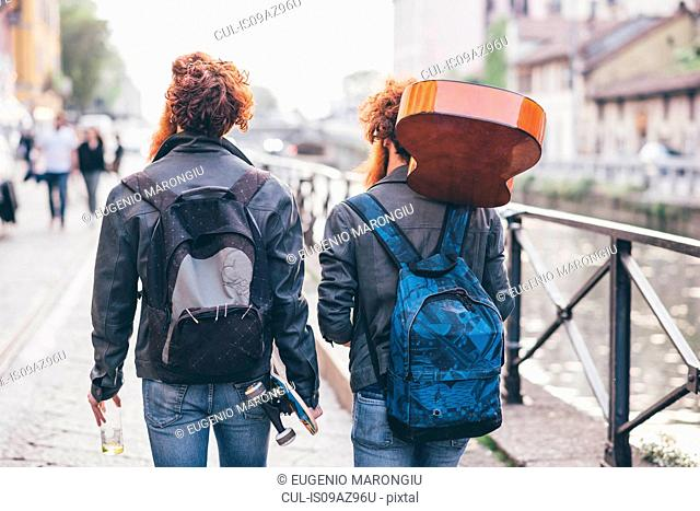 Rear view of young male hipster twins with red hair strolling along canal waterfront