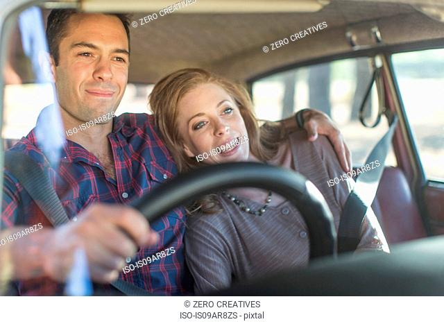 Heterosexual couple in car together, smiling
