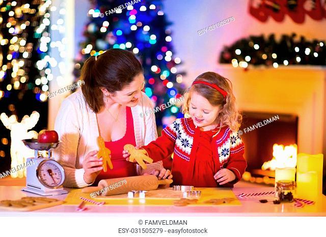 Mother and little girl baking Christmas pastry. Children bake gingerbread. Toddler child preparing cookie for family dinner on Xmas eve