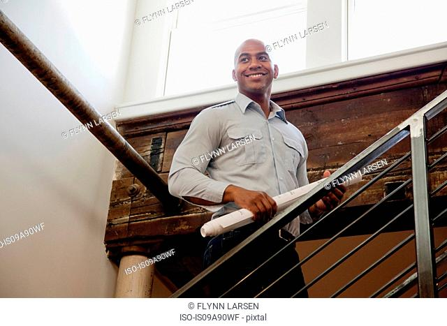 Mid adult man holding rolled up plans on staircase, smiling