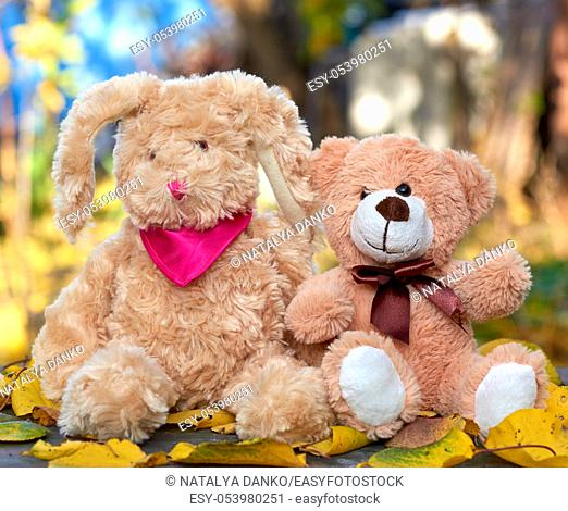 little teddy bunny with long ears and a teddy bear are sitting in the middle of dry yellow leaves on an autumn day, blurred background behind