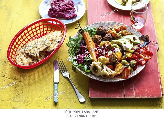 Beetroot hummus, falafel, flat bread, mezze, mutabal, olives, peppers, pommigranet, roast carrots, roast cauliflower, roast potates, salad