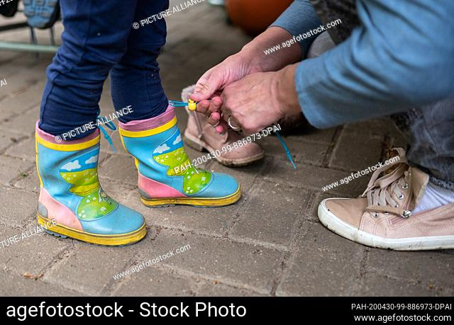 28 April 2020, Lower Saxony, Lüneburg: Emeli has her mother Melanie help her put on rubber boots. In view of the closed playgrounds in Lower Saxony