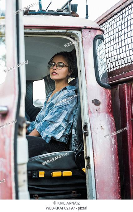 Young woman sitting in cabin of a broken vintage truck
