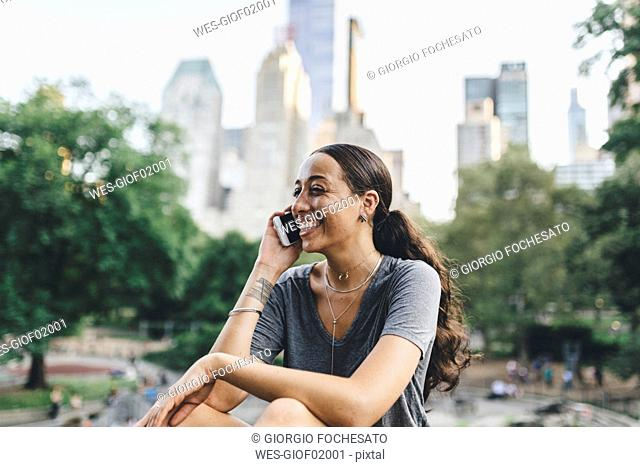 USA, Manhattan, portrait of young woman on the phone in Central Park