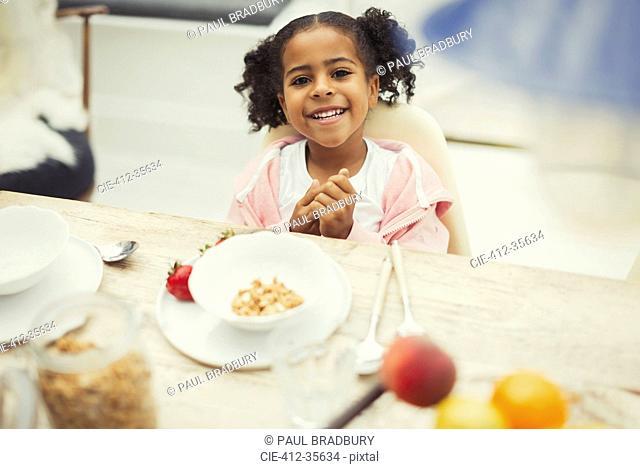 Portrait smiling girl eating breakfast at table