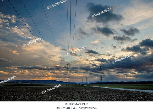 electricity pylons and sky with clouds