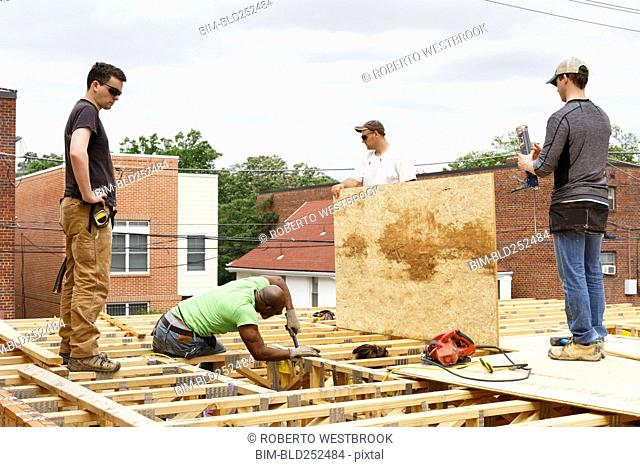 Volunteers working on the roof at construction site