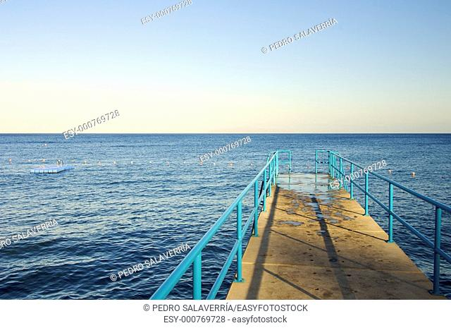 pier at sunset on a calm blue sea in Madeira Island, Portugal