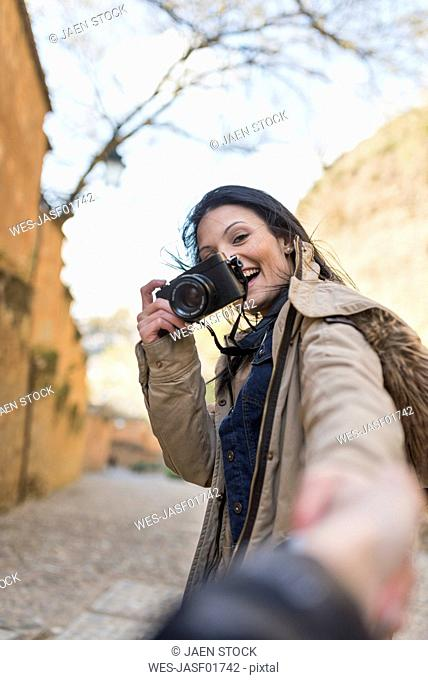 Happy young woman with camera holding hand of boyfriend