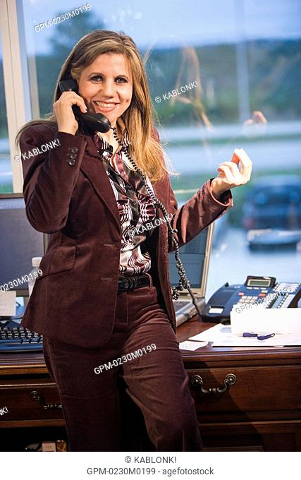 Portrait of mature businesswoman using landline phone in office, smiling
