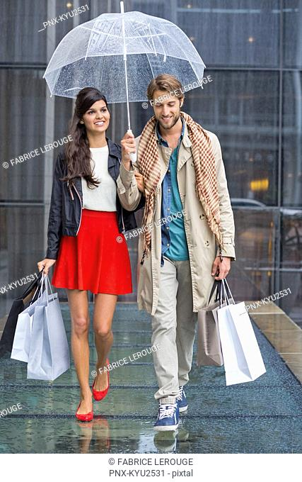 Couple with shopping bags sheltering under umbrella in rain