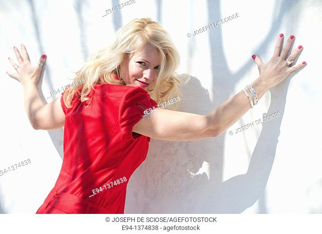 Portrait of a smiling 44 year old blond woman, outdoors looking over her shoulder with arms spread on to a white wall