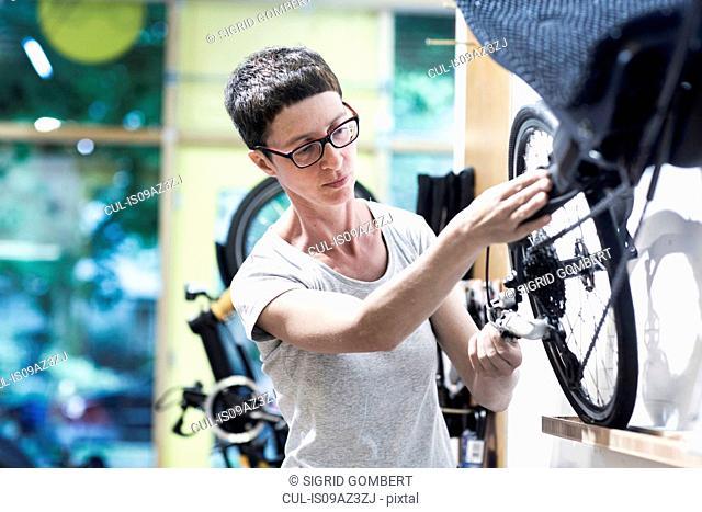 Woman in bicycle workshop repairing wheel on recumbent bicycle