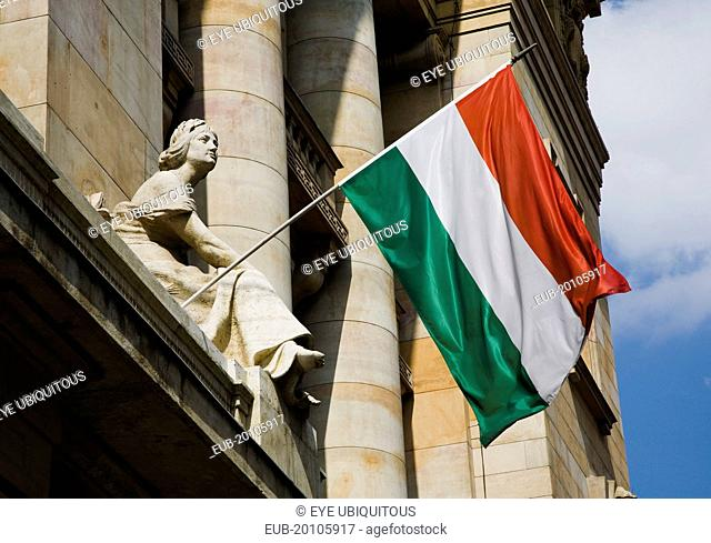 Hungarian Flag flying with Art Nouveau facade behind in central Pest