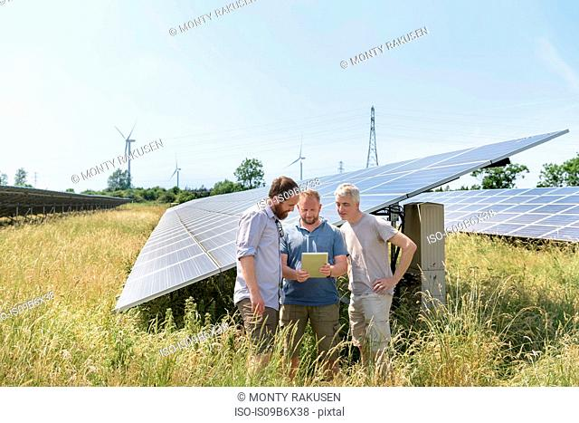 Local community members using digital tablet app to look at energy performance of solar farm