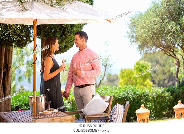 Couple with champagne on boutique hotel patio, Majorca, Spain