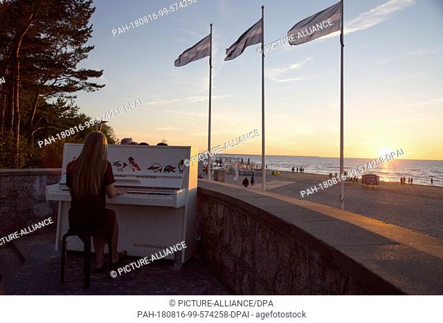 13 August 2018, Latvia, Jurmala: A young woman plays piano in the setting sun at the Latvian Baltic Sea beach Jurmala. With a panoramic view of the sea