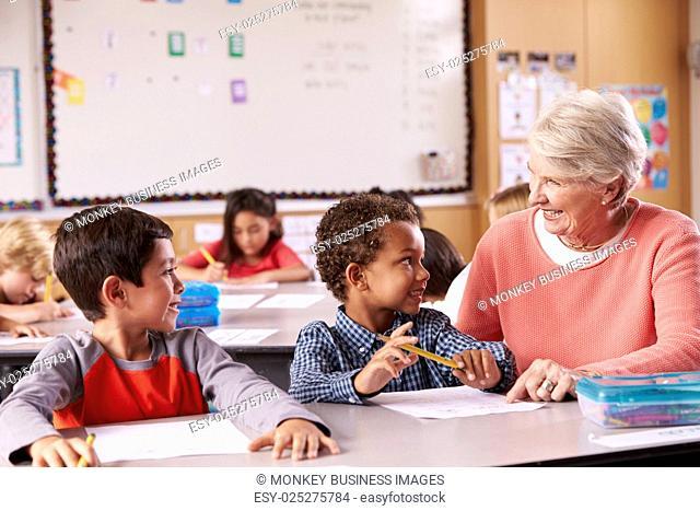 Senior teacher sitting with elementary school kids in class