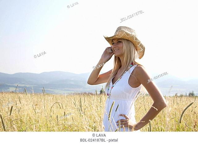 portrait of young woman standing in field talking on mobile phone