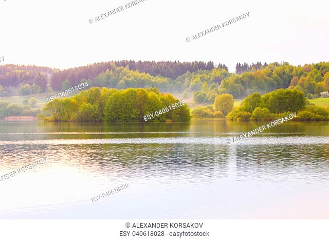 Autumn landscape in the countryside. Green and yellow trees, thick forest surrounding local lake in Belarus. Surface of water ripples reflecting lush vegetation