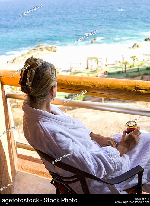 Adult woman sitting with a drink on a hotel balcony overlooking a blue ocean and white sand beach