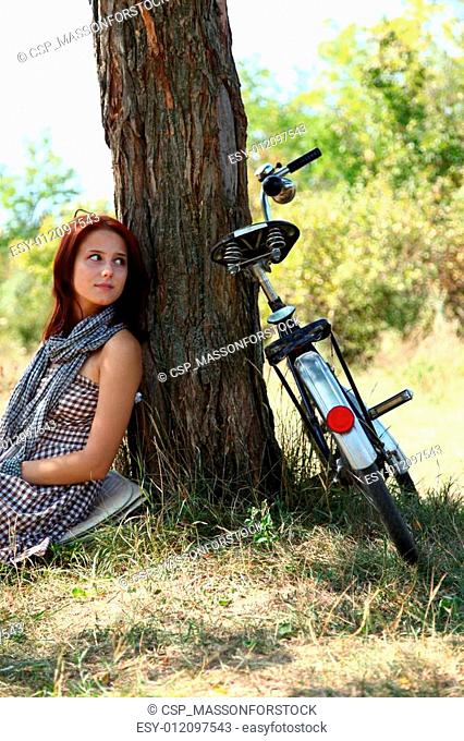 Beautiful girl sitting near bike and tree at rest in forest