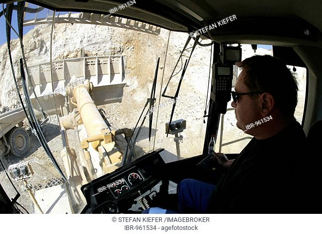 Driver in the driver's cab of a wheel loader, quarrying lime stone in a stone pit for the production of cement in the Schwarzenfeld cement works of the...