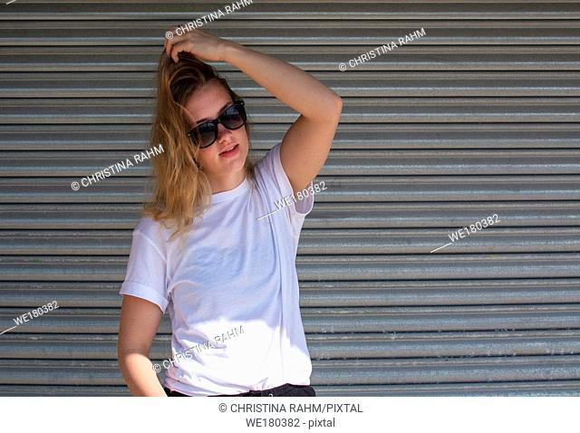 Young casual sporty dressed blonde woman with sunglasses in white t-shirt against corrugated iron wall street style
