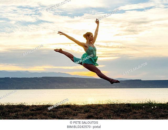 Caucasian ballerina jumping on beach