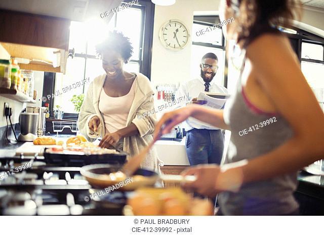 Friend roommates cooking breakfast in kitchen