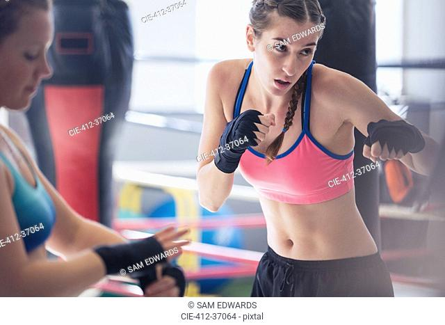 Determined, tough young female boxer shadowboxing in gym