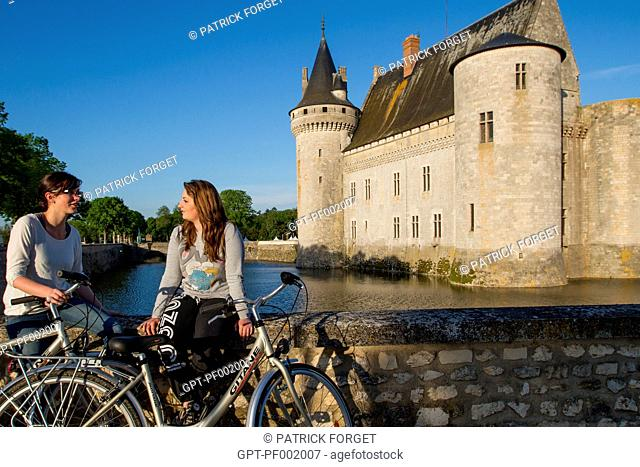 YOUNG WOMEN CYCLING ALONG THE 'LOIRE A VELO' CYCLING ITINERARY IN FRONT OF THE CHATEAU OF SULLY-SUR-LOIRE, LOIRET 45, FRANCE