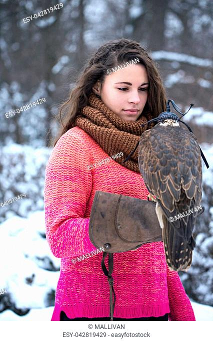 Beautiful woman holding a falcon on her hand in winter