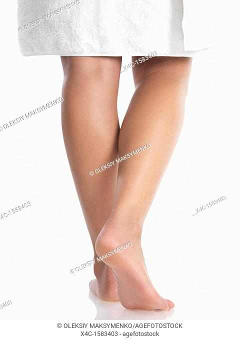 Closeup of legs of a young woman wrapped in a towel  Isolated on white background