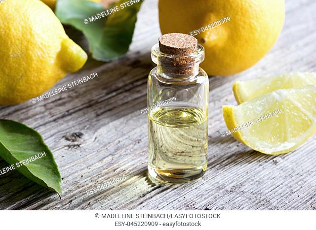 A bottle of essential oil with fresh lemons