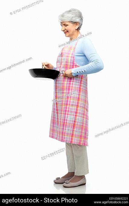 smiling senior woman in apron with frying pan