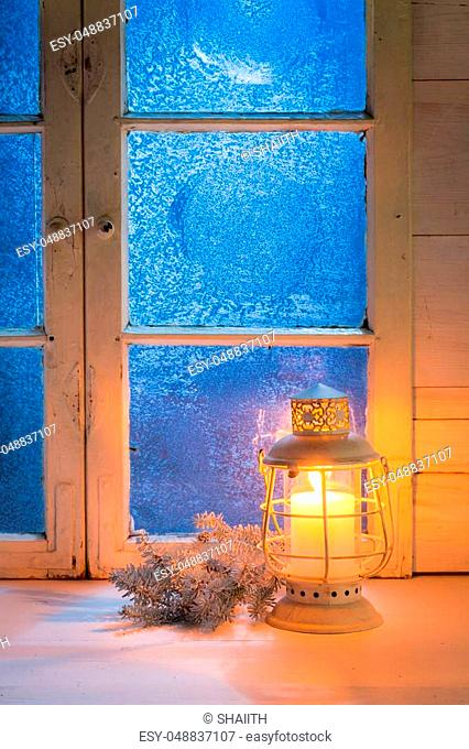 Frosted blue window with candle for Christmas on white table