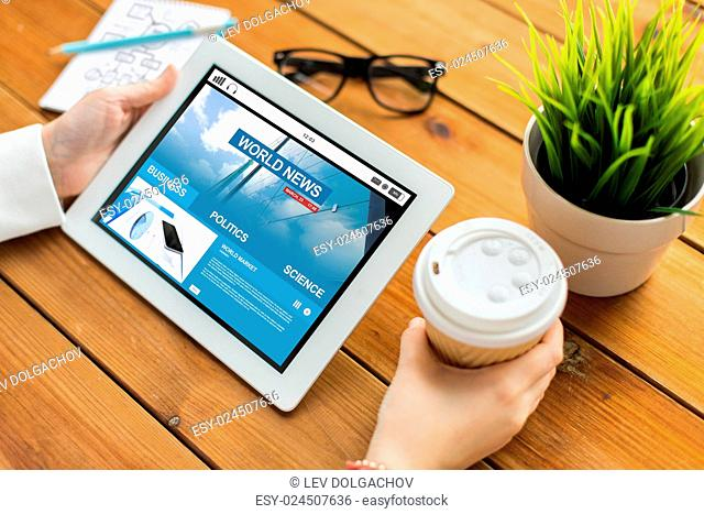 business, mass media, technology, people and advertisement concept - close up of woman with world news web page on tablet pc computer screen and coffee cup on...