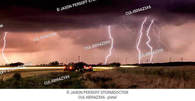 Cloud-to-ground lightning bolts and storm chasers tracking tornadic thunderstorm