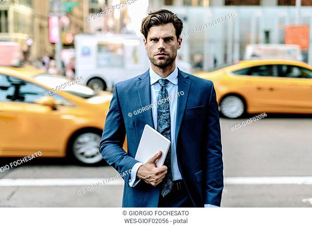 Handsome businessman walking in Manhattan, carrying digital tablet