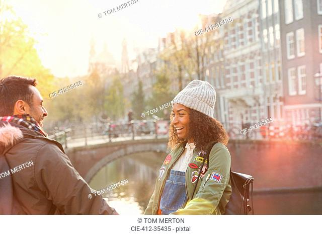 Young couple on urban autumn bridge over canal, Amsterdam