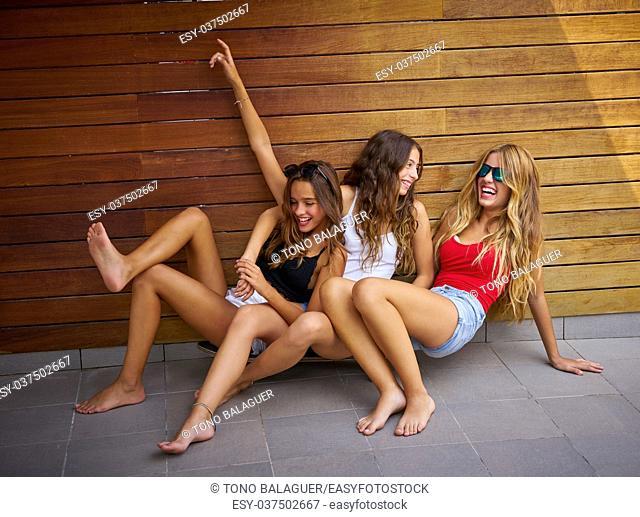Teen best friends girls having fun falling down smiling on a wooden wall