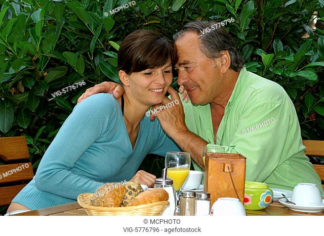 Ein aelterer Mann umarmt seine junge Freundin am Fruehstueckstisch, 2006 - Germany, 31/07/2006