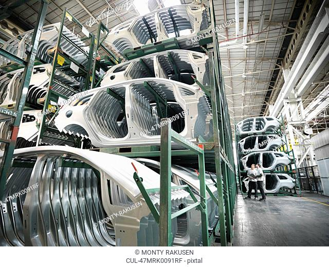 Engineers with pressed car parts in car factory