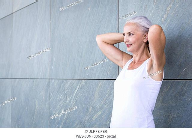 Smiling woman with hands behind her head standing in front of a wall