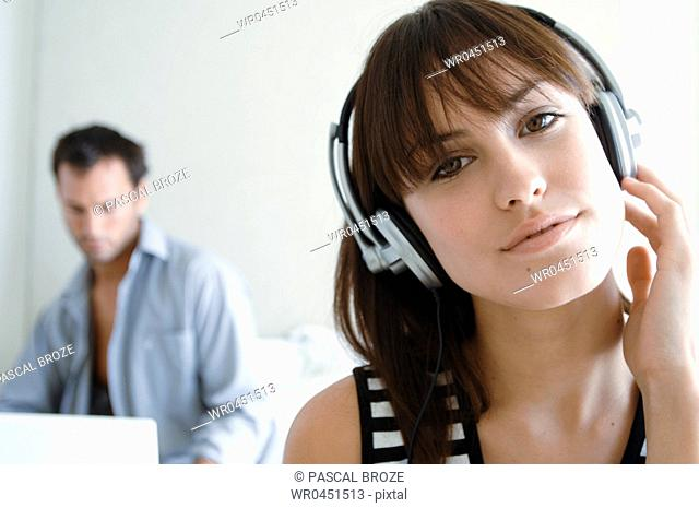Close-up of a young woman listening to music with a young man using a laptop in the background