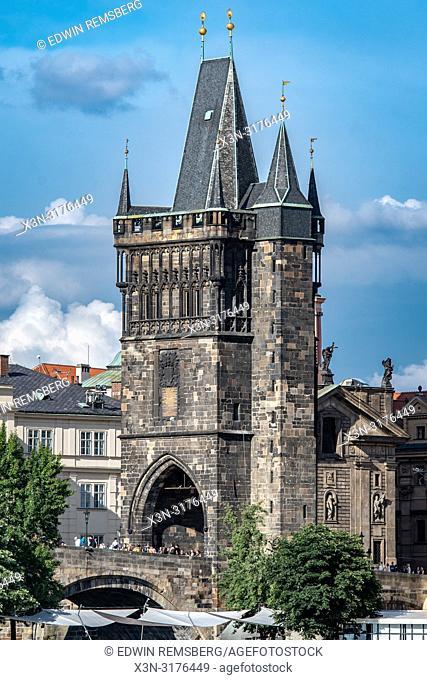 Distant view of pedestrians walking through the bridge tower of Charles Bridge in Prague - Czech Republic