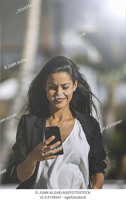 Trendy brunette in black jacket surfing smartphone on territory of tropical resort walking in sunlight