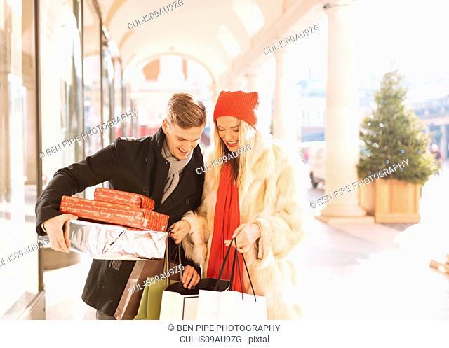 Young couple looking at xmas gifts in Covent Garden, London, UK